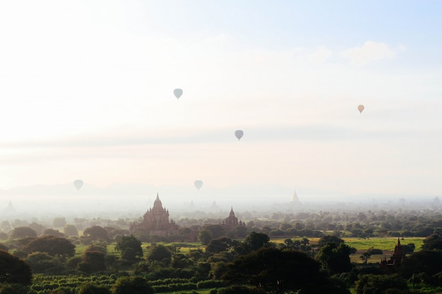Fantasy concept - hot air balloons flying over temples and castles over a beautiful field in the sky