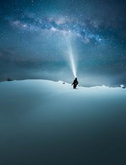 손전등으로 아름다운 별이 빛나는 하늘을 비추고 조명하는 여행자의 판타지 컨셉