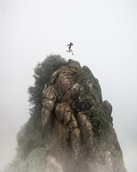 Fantasy concept - a person jumping over a high rocky cliff with a blurred foggy white background
