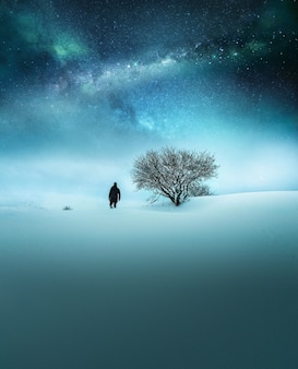Il concetto di fantasia di un viaggiatore si è vestito nell'esplorazione nera nella neve con il cielo stellato strabiliante