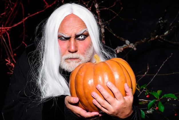 판타지 공포 할로윈. 호박과 무서운 남자입니다. 잭오랜턴 만들기. 휴일 의상에서 잘생긴 남자입니다.