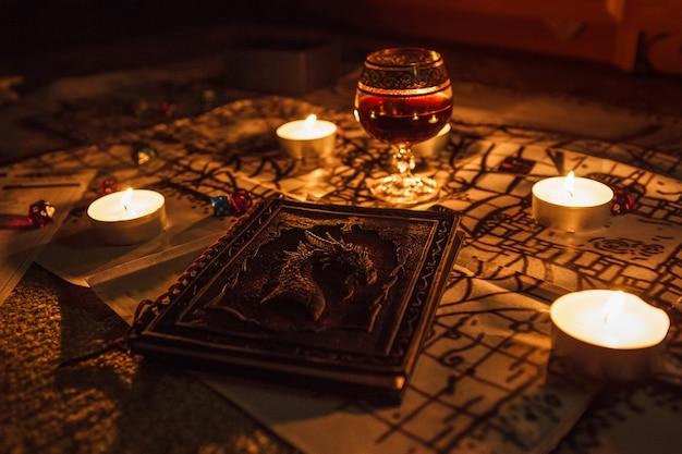 Книга в стиле фэнтези со свечами и бокалом красного вина