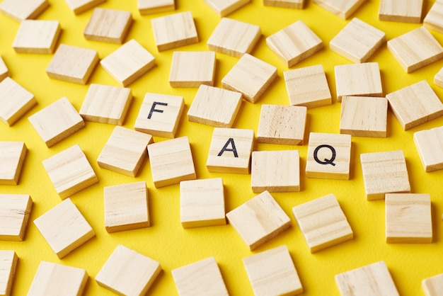 Деревянные блоки с словом faq на желтом baclground. часто задаваемый вопрос