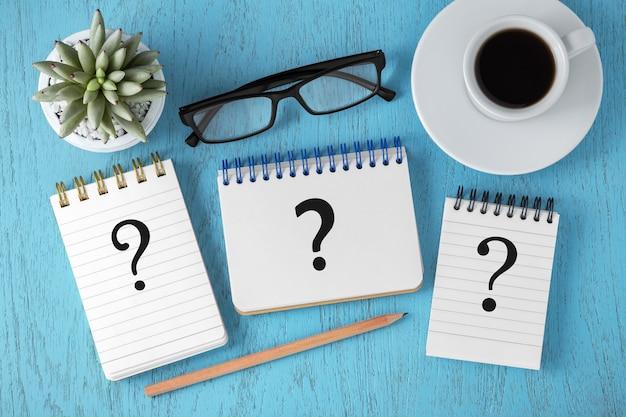 Концепция часто задаваемых вопросов с вопросительными знаками на блокнотах