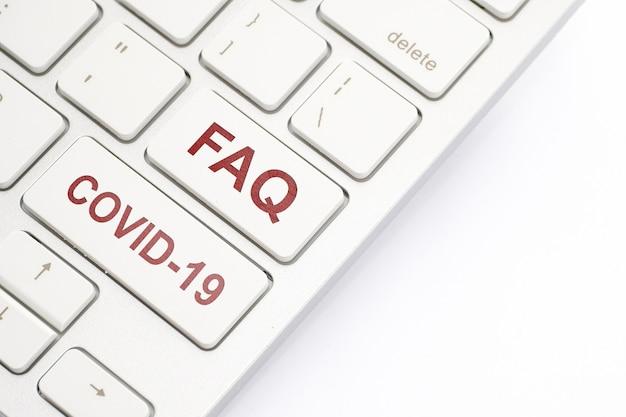 Клавиатура с надписью faq и covid-19.
