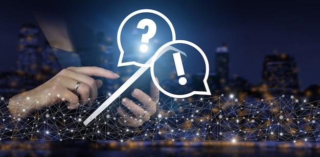 Faq 자주 묻는 질문 개념입니다. 도시의 어두운 배경에 디지털 홀로그램 물음표 기호가 있는 손으로 터치하는 흰색 태블릿. 문제, 도움 및 조언 개념이 필요합니다.