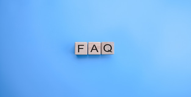 Faq word on the wooden cubes on blue background