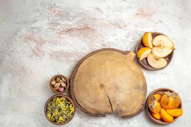 Inquadratura lontana di un piatto di legno e una ciotola di lavanda secca, fiori e frutta su marmo