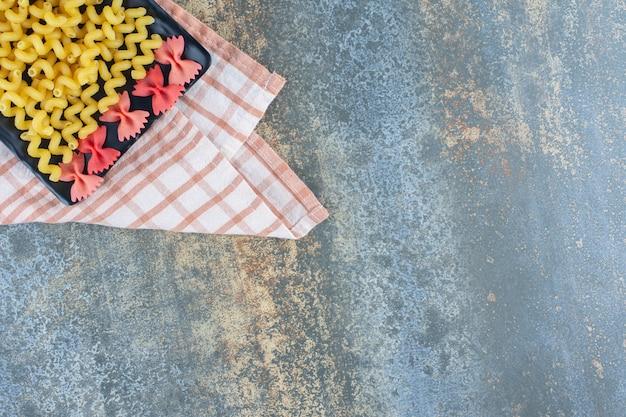 Фарфалле и фигурные макароны на тарелке, на полотенце, на мраморном фоне.