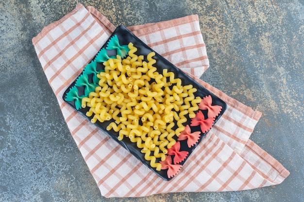 Фарфалле и фигурные макароны на тарелке, на полотенце, на мраморной поверхности.