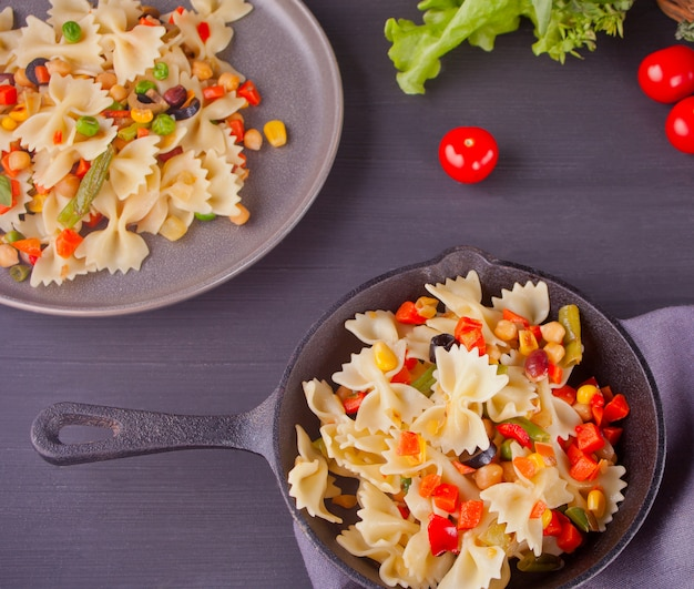 Farfalle italian pasta with mix vegetables on a iron black pan
