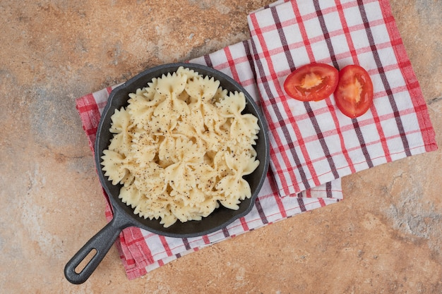 Фарфалле на черной сковороде с ломтиками помидора. качественная иллюстрация