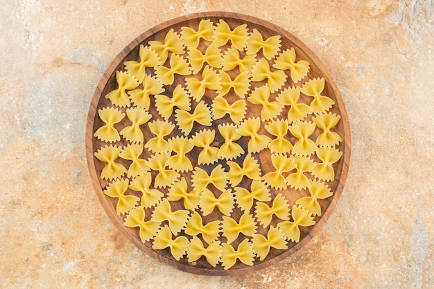 Макароны фарфалле на деревянной тарелке на синей поверхности