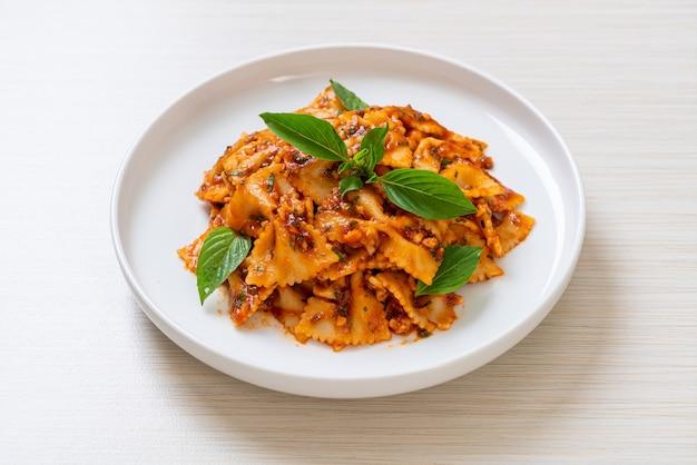 Макароны фарфалле с базиликом и чесноком в томатном соусе. итальянский соус