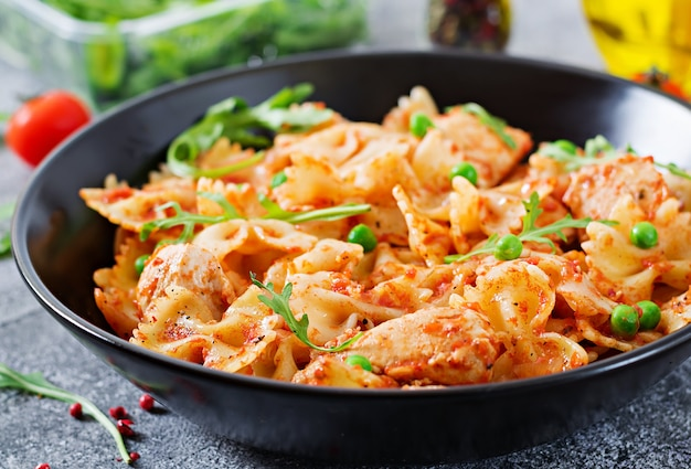 Farfalle pasta with chicken fillet, tomato sauce and green peas.   food menu