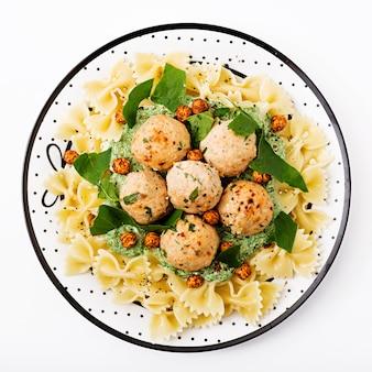 Паста фарфалле с фрикадельками и шпинатным соусом с жареным нутом.