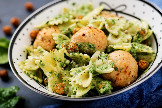 Farfalle pasta with meatballs and spinach sauce with fried chickpeas.