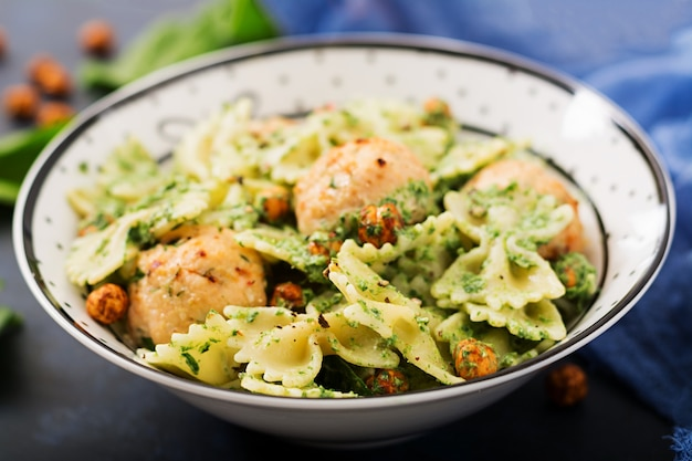 Farfalle pasta with meatballs and spinach sauce with fried chickpeas