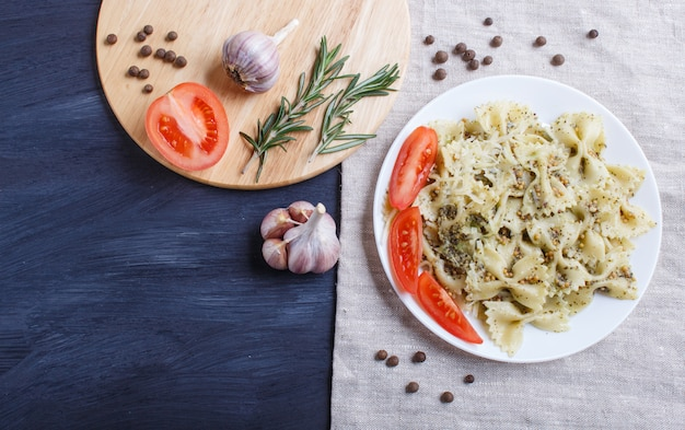 Farfalle pasta with pesto sauce, tomatoes and cheese on a linen tablecloth on black