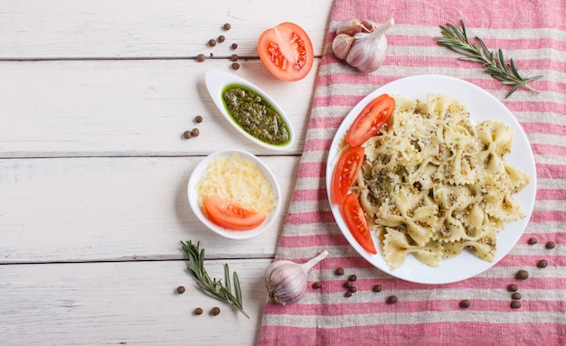 Farfalle pasta with pesto sauce, tomatoes and cheese on a linen tablecloth on white