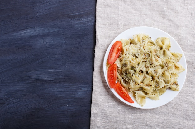 Farfalle pasta with pesto sauce, tomatoes and cheese on a linen tablecloth with copyspace
