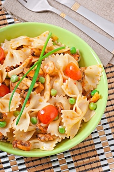 Farfalle pasta with seafood, cherry tomatoes and green peas