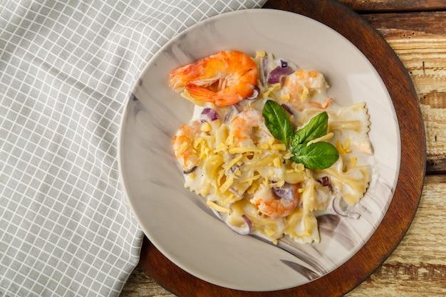 Паста фарфалле с креветками в сливочном соусе на серой тарелке на деревянном столе на светлой салфетке. горизонтальное фото