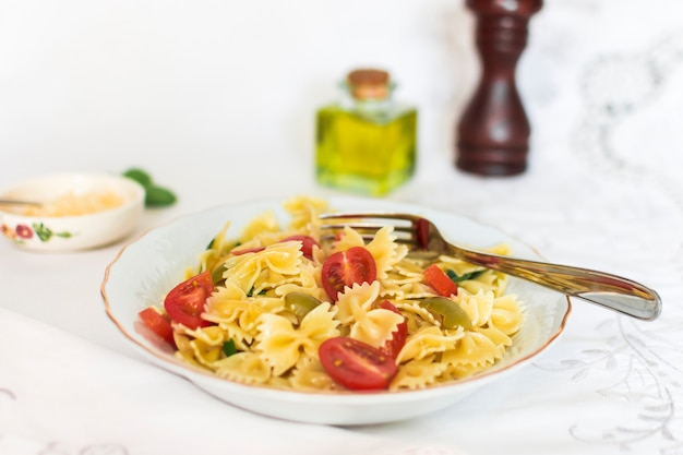 Farfalle pasta with tomato and olive slices on ceramic plate