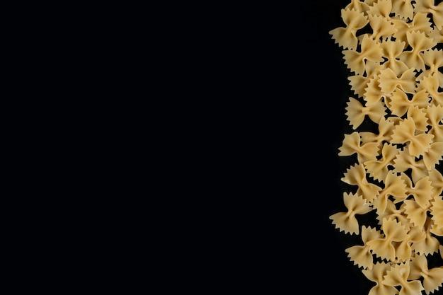 黒い背景にファルファッレ生パスタ。料理のコンセプトです。コピースペースの平面図。