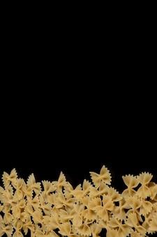 黒い背景にファルファッレ生パスタ。料理のコンセプトです。コピースペースの平面図
