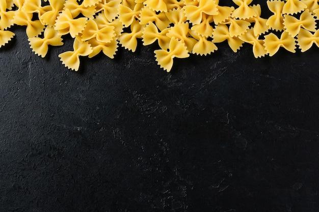黒いコンクリートのテーブルにファルファッレの生パスタ。料理のコンセプト。コピースペースのある上面図。