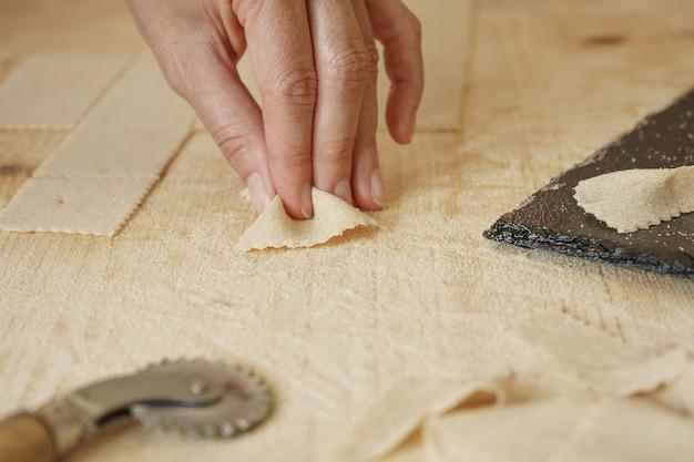 Закройте вверх по детали макроса процесса домодельных макаронных изделий farfalle vegan. повар формирует тесто