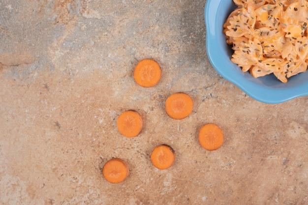オレンジ色の背景にチーズソースとニンジンのスライスとファルファッレ。高品質のイラスト