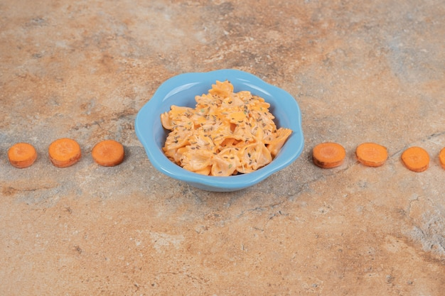 Farfalle with cheese sauce and carrot slices on orange background. high quality illustration