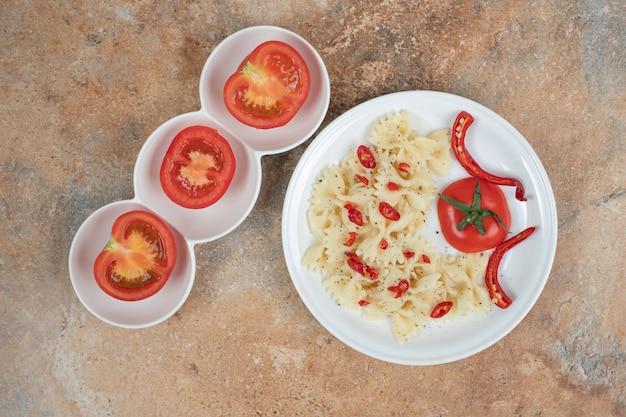 Фарфалле с перцем чили и помидорами на белой тарелке. качественная иллюстрация