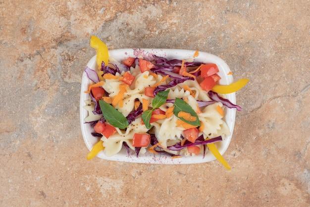 Фарфалле с ломтиками свежих овощей в белой миске.