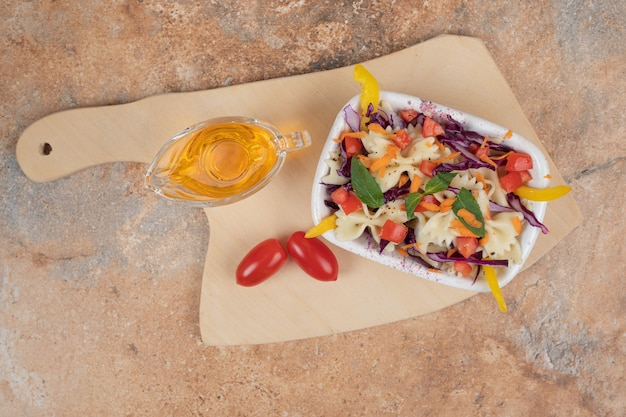 Farfalle with fresh vegetable slices and oil on wooden board. high quality illustration