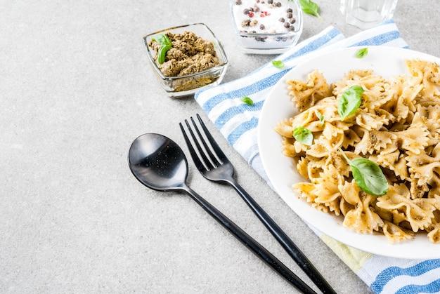 白い皿にペストソースとバジルの葉とファルファッレ
