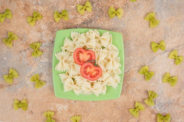 Фарфалле с ломтиками помидора на зеленой тарелке.