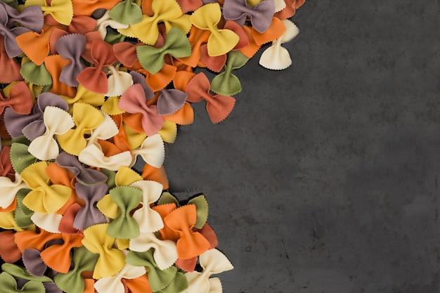 Итальянский сырцовый пестротканый farfalle макароны крупным планом на черном фоне с копией пространства.