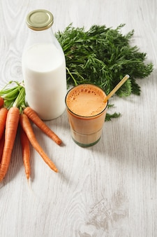 Farm carrot harvest lying near milk bottle and glass filled with mix natural fresh juice and milk with golden drinking straw in it