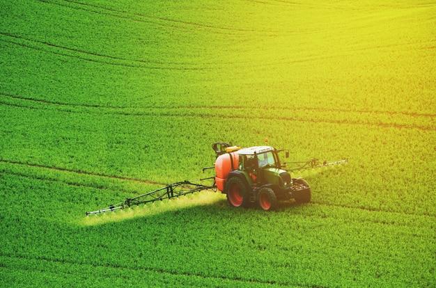 농기계는 녹색 들판에 살충제를 뿌리고, 농업의 자연 계절 봄 배경