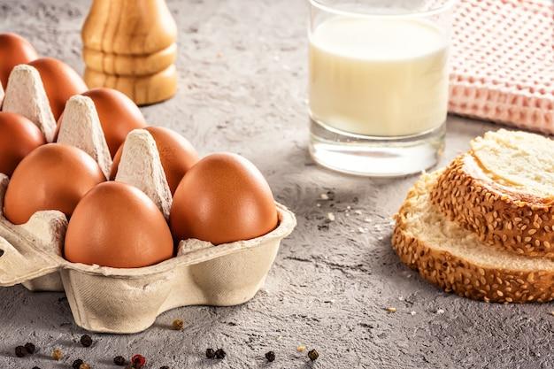 Farm raw fresh egg in pack bread milk on gray table ingredient for breakfast preparation