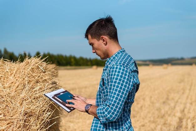 フィールドの農家農学者はタブレットを使用しています