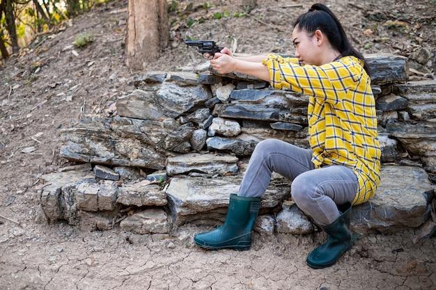 농장에서 오래된 리볼버 총에서 총격 사건에서 부츠를 신은 농부 asea 여자
