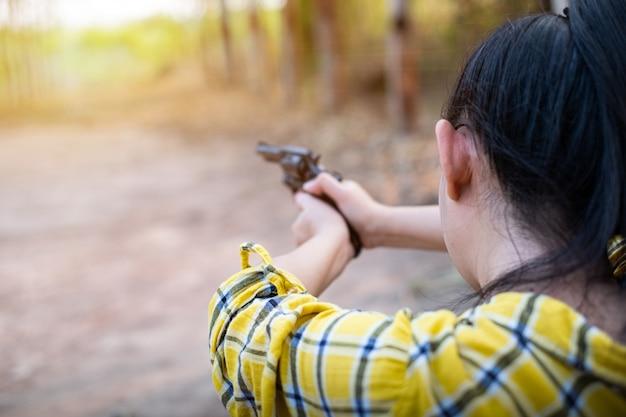 농장에 있는 오래된 리볼버 총에서 총격을 가할 때 노란색 셔츠를 입은 농부 아시아 여성