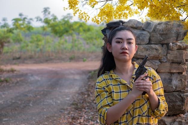 농장에서 오래된 리볼버 총을 들고 노란색 셔츠를 입은 농부 asea 여자
