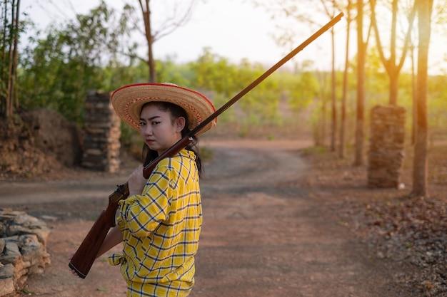 총구 장전 빈티지 총에서 촬영 범위에서 모자를 쓰고 농부 아시아 여자