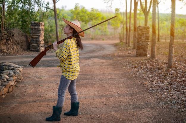농장에서 총구를 든 빈티지 총을 들고 모자를 쓰고 있는 농부 아시아 여성