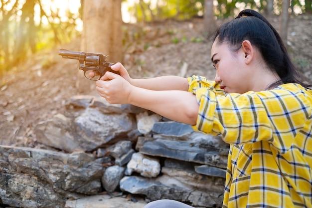 농장에서 오래된 리볼버 총에서 총격 사건에서 셔츠를 입은 농부 아시아 여성